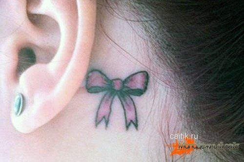 татуировка бантик за ухом